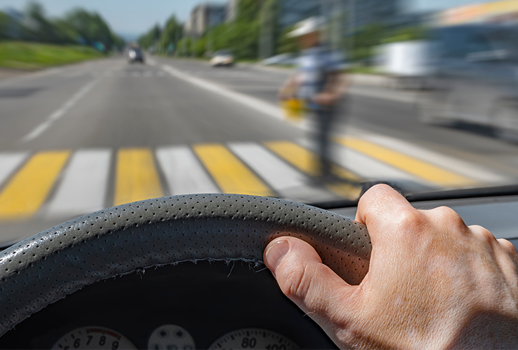 the driver hand on the steering wheel of a car moving at high speed and passing a pedestrian crossing with the risk of hitting a person